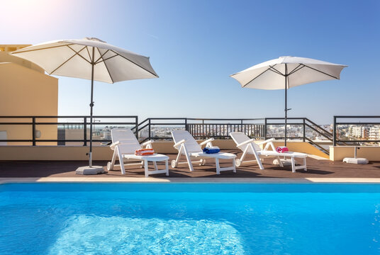Loungers placed on the right and in the front of a pool with clean looking water on a sunny day.