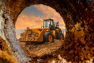 Fototapeta Wheel loader are digging the soil in the tunnel construction site on the sky background obraz