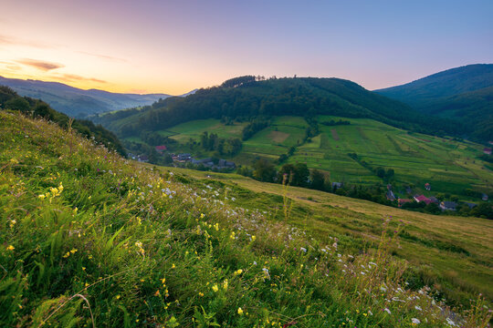 rural valley landscape at dawn. beautiful carpathian nature scenery with grassy hills, fields and meadows between forested hills. small village in the distance. cloudless sky