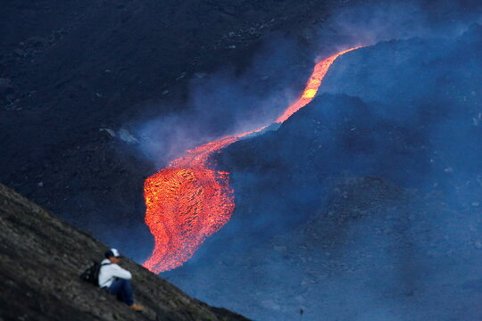 A man sits as red hot lava flows during an eruption of the Pacaya volcano at San Vicente de Sales municipality in the Escuintla region