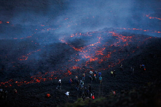 People watch as streams of red hot lava flow during an eruption of the Pacaya volcano at San Vicente de Sales municipality in the Escuintla region