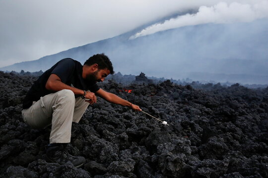 A man roasts marshmallows over volcano lava during an eruption of the Pacaya volcano at San Vicente de Sales municipality in the Escuintla region