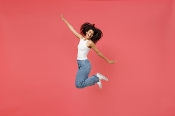 Full length young fun overjoyed joyful cheerful positive african american woman 20s in casual white tank shirt jump high with outstretched hands arms isolated on pink color background studio portrait. - fototapety na wymiar