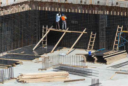 Workers make metal reinforcement for the concrete foundation.