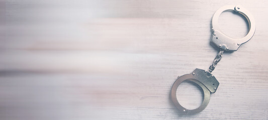 Isolated handcuffs, banner and copy space on a wooden background. - fototapety na wymiar