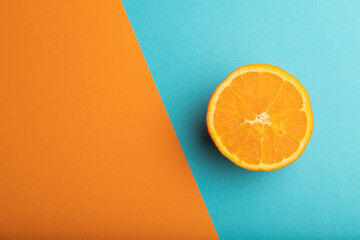 Ripe cut orange on orange and blue pastel background. Top view, copy space.
