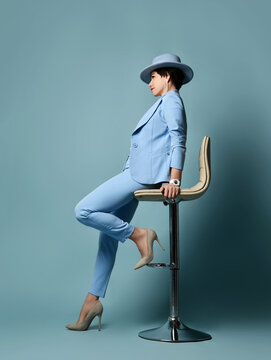 Stylish short haired brunette woman in blue official suit, hat and high-heeled shoes sitting on bar stool over blue background. Full-growth. Side view. Stylish female wear and fashion concept