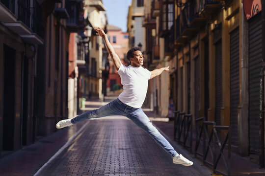 Happy black guy doing an acrobatic jump in the middle of the street.