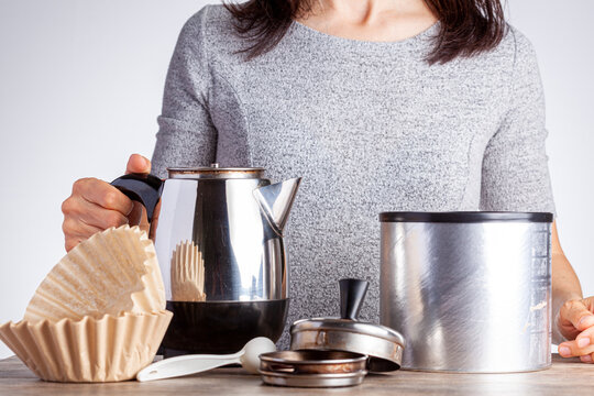 A young caucasian woman is preparing coffee on table using a percolator filter papers and a jar of coffee. She is against white background. Homemade morning coffee concept.