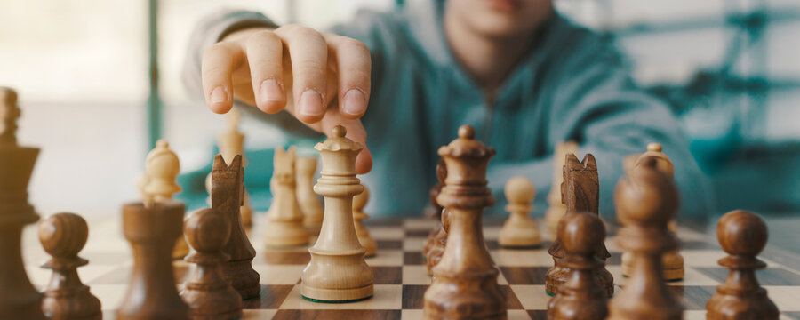 Boy playing chess and moving a piece