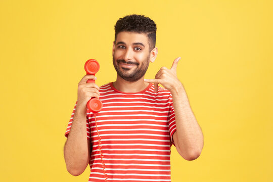 Positive bearded man in striped t-shirt holding red headset of retro landline telephone and showing call me gesture, 24/7 call centre. Indoor studio shot isolated on yellow background