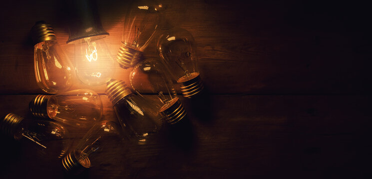 stand out in a crowd. leadership and uniqueness concept. glowing filament light bulb on wooden background. copy space