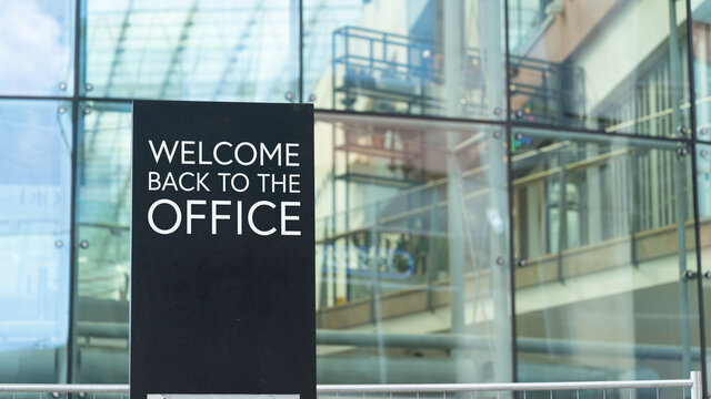 Welcome back to the office on a city-center sign in front of a modern office building