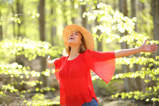 Excited woman spreading in a green forest a sunny day