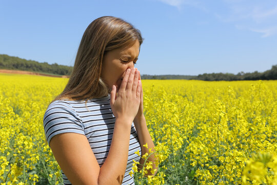 Allergic woman coughing in a yellow field