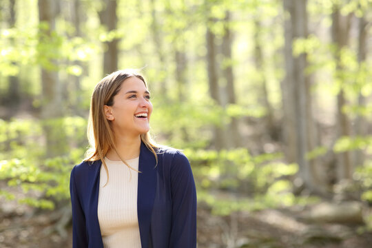 Happy woman contemplating views in a beautiful forest