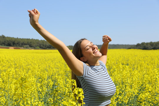 Happy woman stretching arms in a field in spring