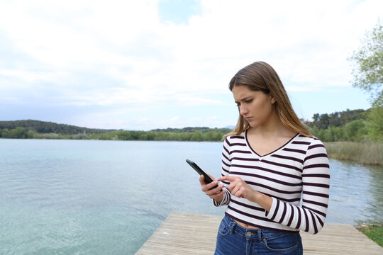 Sad woman reading message on phone on vacation