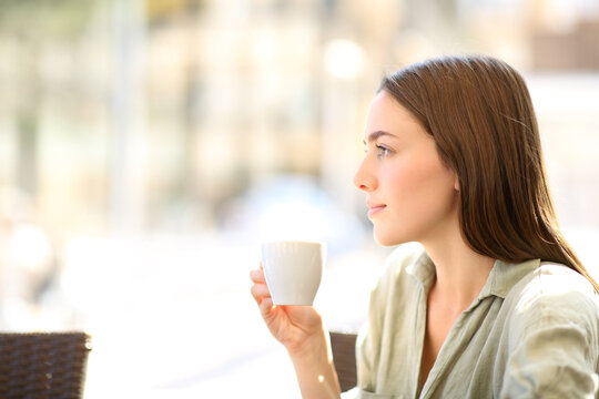Woman drinking coffee looking away in a bar