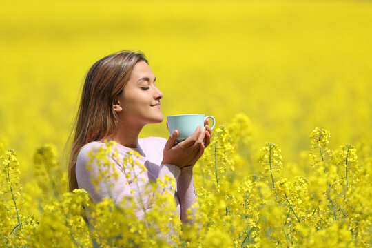 Woman drinking coffee in the middle of a yellow field