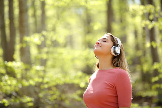 Woman meditating wearing headphones in a forest