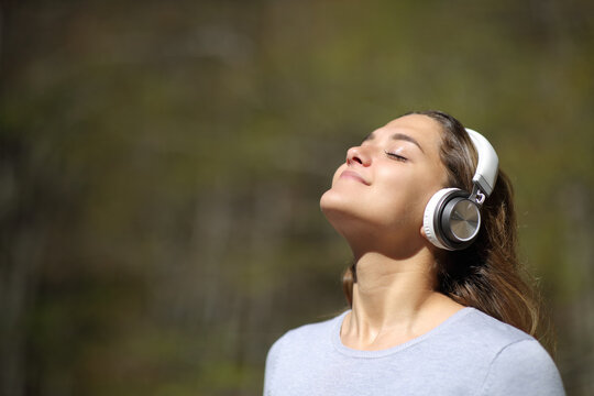 Woman meditating wearing headphones in a park