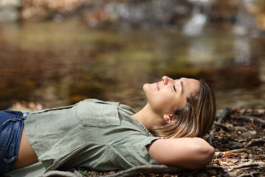 Woman relaxing resting lying in a riverside