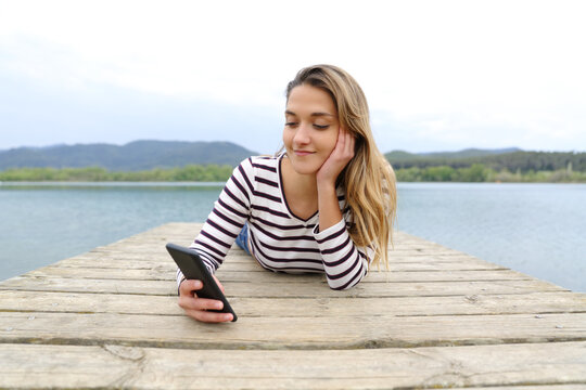 Woman checking smart phone in a lake