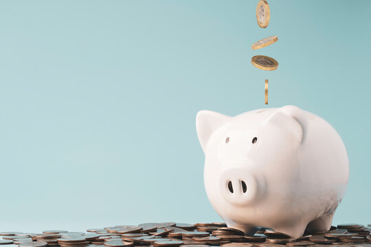 Coins falling and dropping to white piggy bank saving on top of heap of coins and blue background ,money saving for investment and retirement in the future concept.