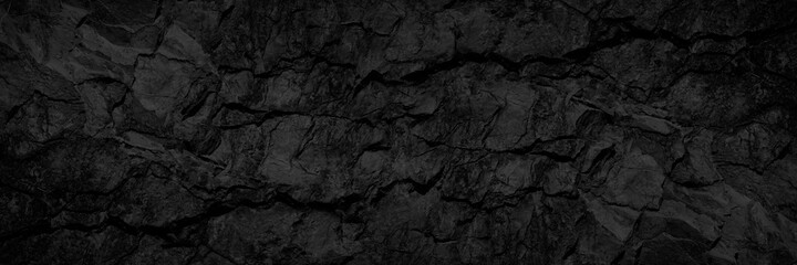Rock texture with cracks. Black stone background with copy space for design. Wide banner. - fototapety na wymiar