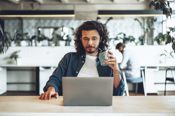 Obraz Young businessman is using laptop and holding a cup of coffee in office - fototapety do salonu