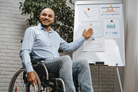 Young african american disabled man in a wheelchair makes presentation at office on whiteboard