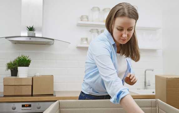 Woman arranges kitchen utensils after moving to new apartment.