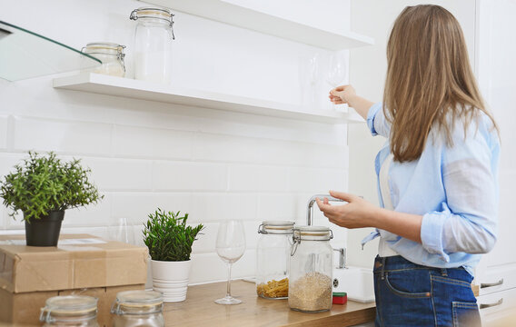 Girl arranges glasses in a new kitchen.