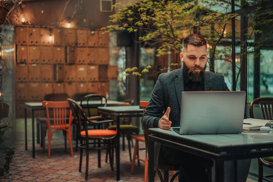 Businessman using a laptop while working remote from a cafe