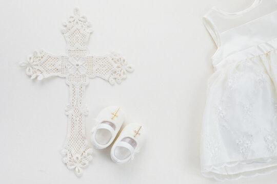 Christening background with baptism dress, shoes, and cross on pastel background