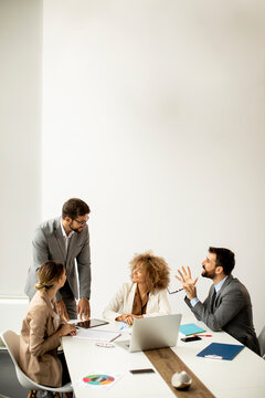 Group of young business people working and communicating while sitting at the office desk together