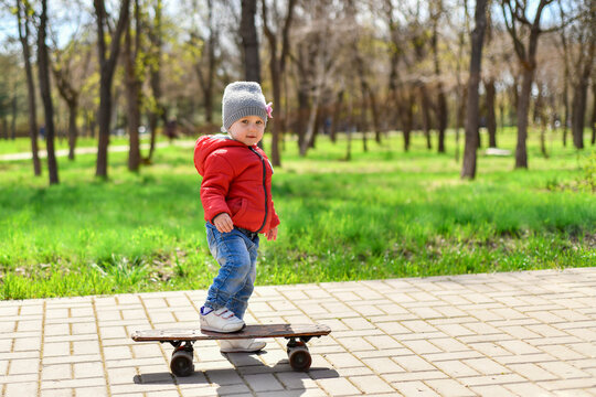 A little girl is riding a skateboard on the sidewalk path in the park.