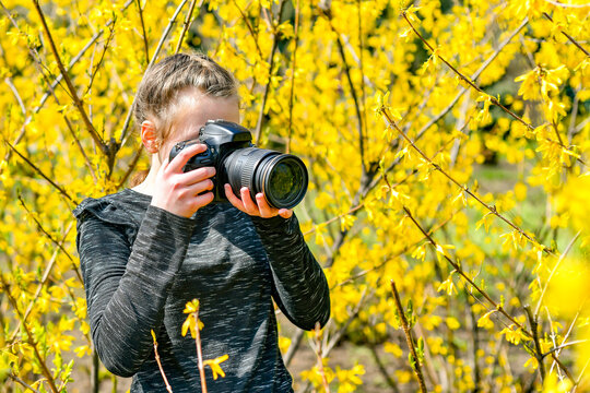 A young girl photographs nature in the park with a SLR camera.