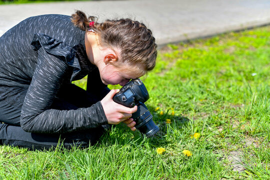 The girl takes a close-up photograph in the park on a SLR camera.