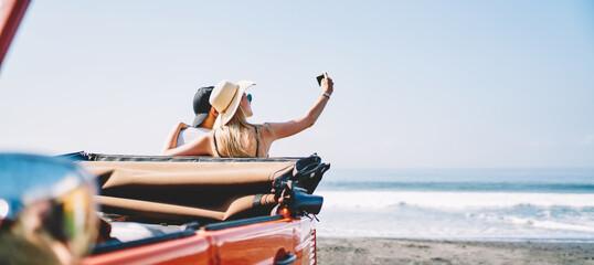 Obraz Couple using smartphone while taking selfie - fototapety do salonu