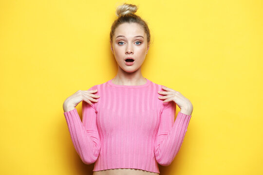 blonde woman wearing pink sweater keeps mouth widely opened, looks at camera