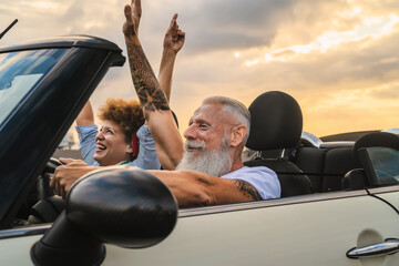 Obraz Happy senior couple having fun driving on new convertible car - Mature people enjoying time together during road trip tour vacation - Travel people lifestyle concept - fototapety do salonu
