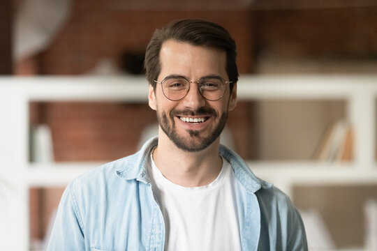 Head shot portrait confident smiling bearded businessman in glasses looking at camera, standing in office, successful happy young man employee entrepreneur posing for photo or recording video