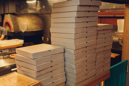 Pizzas cardboard boxes for shipping and delivery. a lot of packaging is on the kitchen stock.