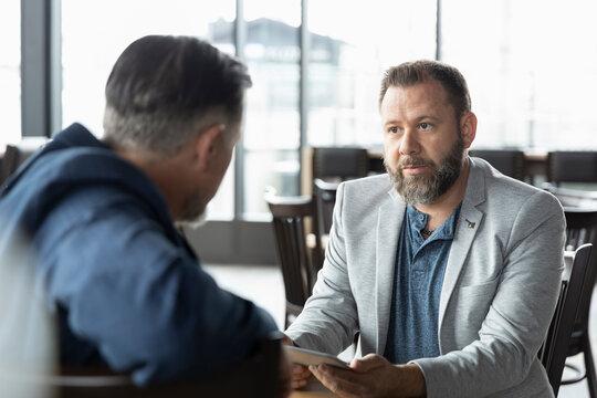 Businessmen meeting and talking in restaurant