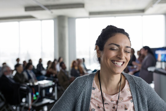 Portrait laughing, enthusiastic businesswoman at conference