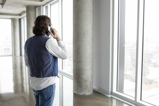 Businessman talking on smart phone in empty office