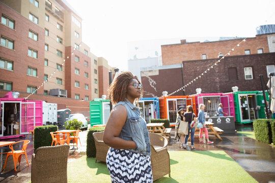 Young woman at sunny urban bazaar marketplace