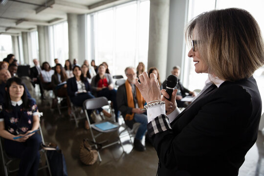 Businesswoman with microphone leading business conference